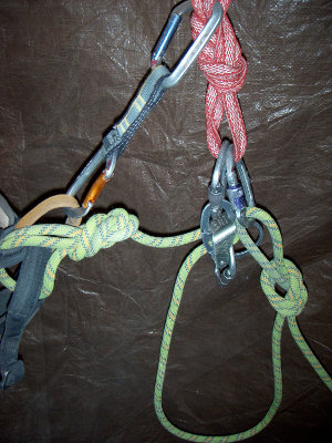 The second climber is secured with an overhand knot behind the belay device and clipped into the anchor.