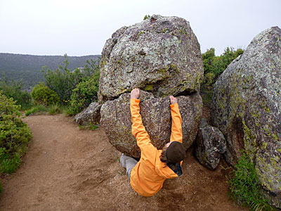 """The author gets a rainy day send on """"The Piranha,"""" an impressively small boulder on the rim of the Black Canyon of the Gunnison. Photo by Jack Cody."""